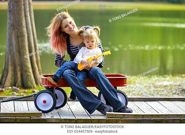 mother and daughter playing toy guitar in the park lake with pull cart