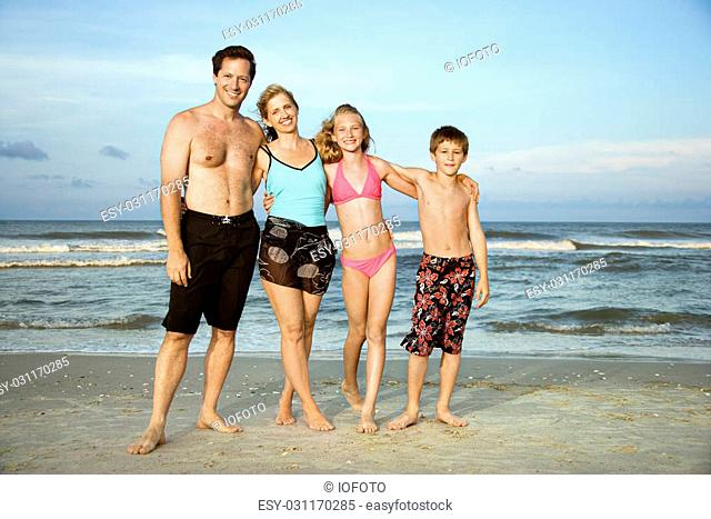 Caucasian family of four standing on beach