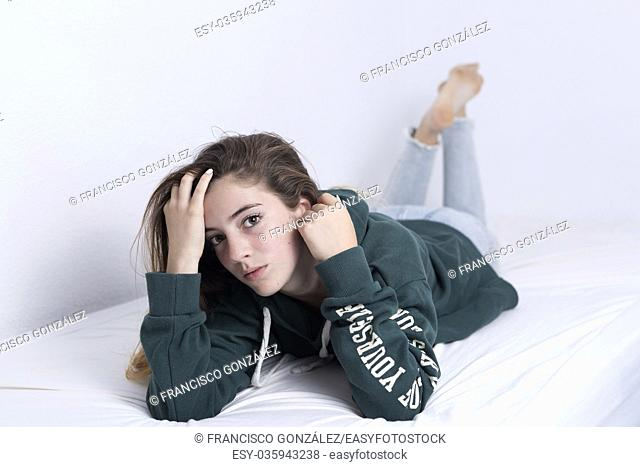 15-year-old adolescent lying on her bed. Studio soft light