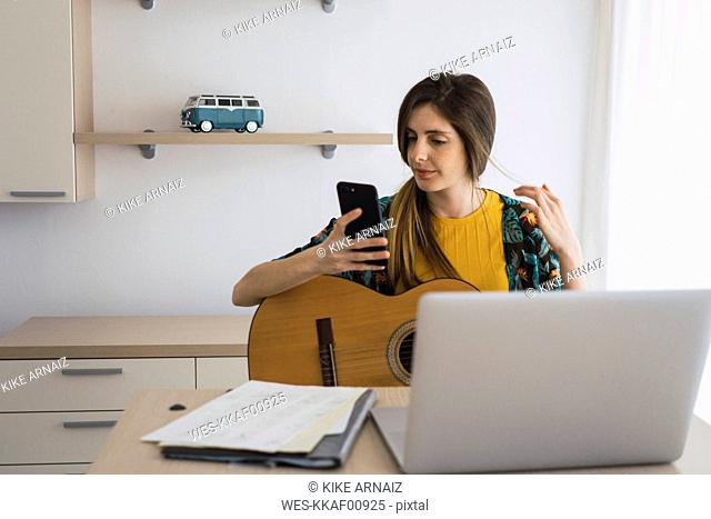 Young woman sitting at table at home with guitar, cell phone and laptop