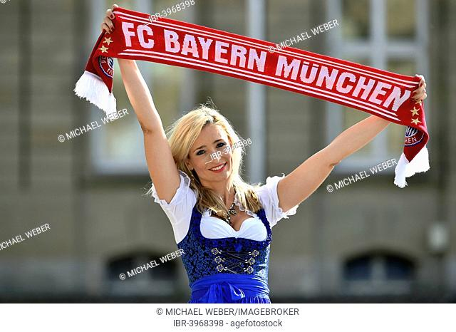 Young woman wearing a dirndl, supporter of FC Bayern, holding up a fan scarf, Germany