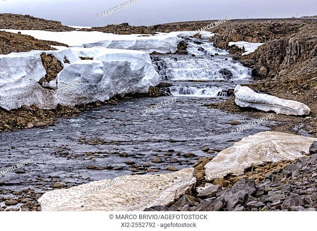 Mountain river and melting snow driving along the road 61 to Isafjordur, in the western fjords of Iceland