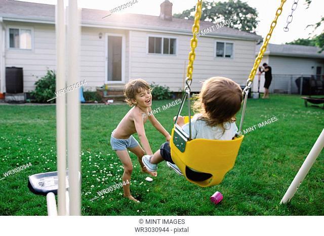 Young bare chested boy with brown hair standing in a garden, pushing young girl sitting on a swing