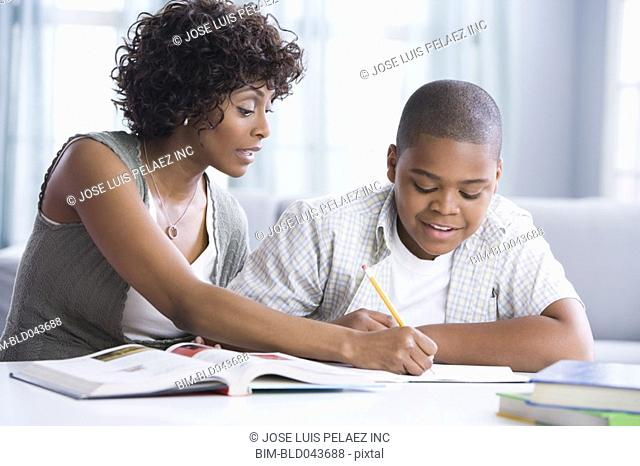 African American mother helping son with homework