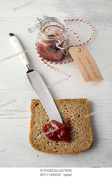 A slice of rye bread with a knife and strawberry jam