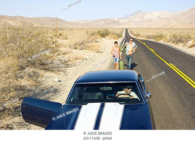 Car with door open for young couple hitchhiking on desert road, elevated view