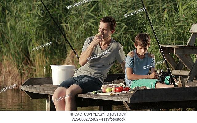 Hipster father and son enjoying picnic by the pond