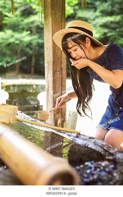 Young woman wearing blue dress and hat using bamboo water hand washing basins at Shinto Sakurai Shrine, Fukuoka, Japan