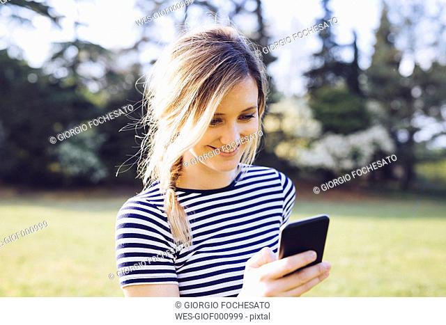 Portrait of smiling blond woman looking at her smartphone