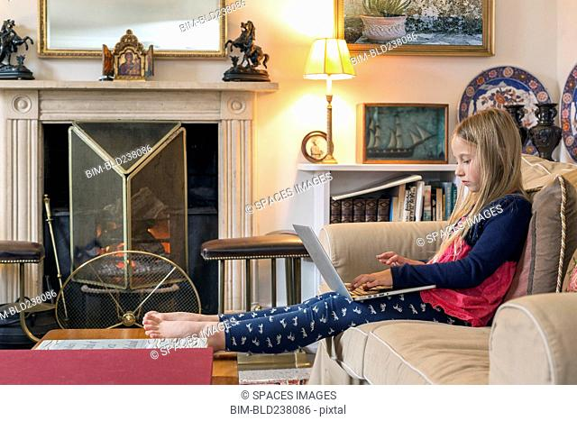 Caucasian girl sitting on sofa using laptop
