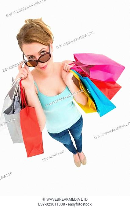 Blonde looking over her sunglasses while holding bags
