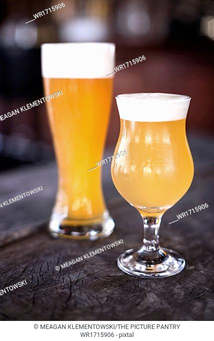 Tulip and weizen glasses of beer on a rustic wood surface with bar in background