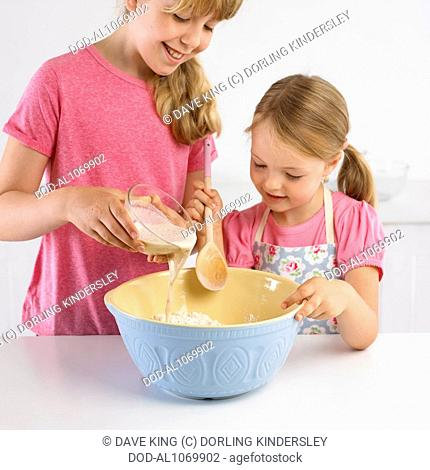 Pouring yeast and water into flour, making bread