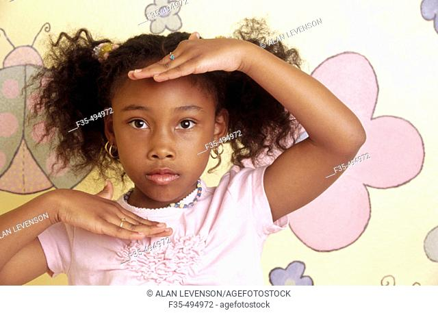 Cute African American girl frames face with hands