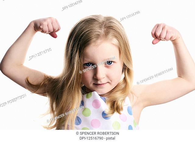 A young girl with blond hair shows her muscles on a white background