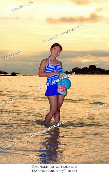 Tourist girl in a blue striped swimsuit pose with happiness on the beach and beautiful landscape of sky over the sea during sunrise at Koh Miang Islands
