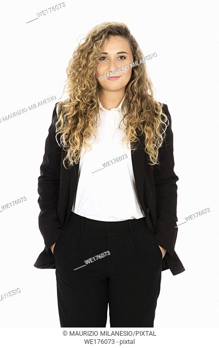 Smiling girl with curly blonde hair, she is standing with her hands in her pocket, wearing a black suit and white shirt