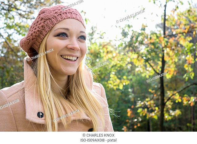 Portrait of young woman wearing knit hat in park