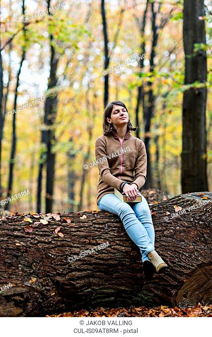 Girl daydreaming on tree trunk in autumn forest