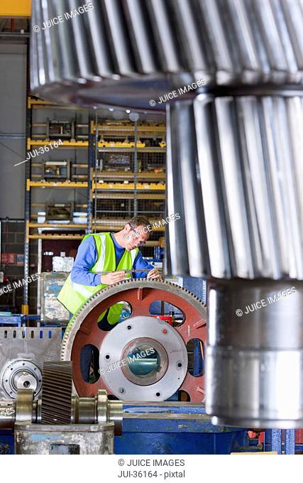 Worker inspecting gear wheels in factory