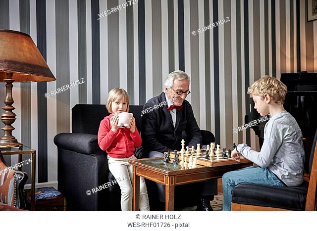 Grandfather and grandson playing chess in living room with girl sitting next to them