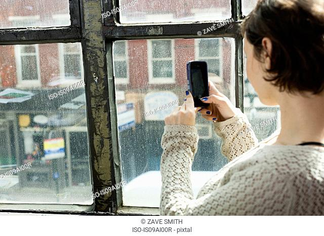 Young woman photographing street below from window