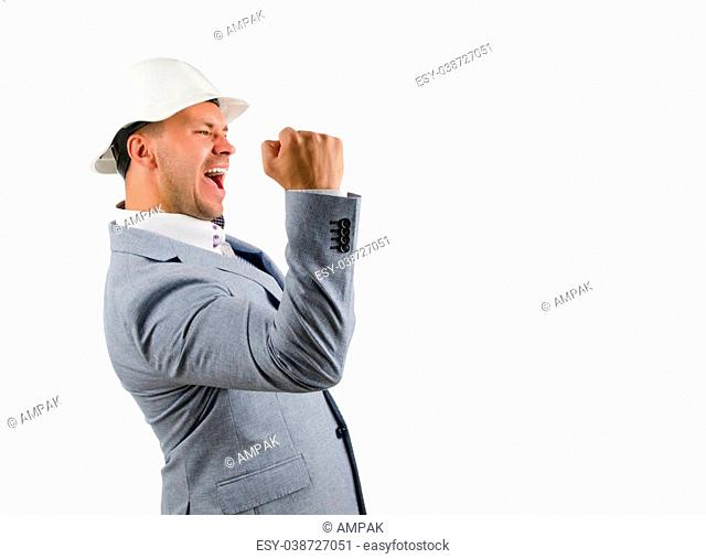 Man wearing a hardhat cheering in jubilation and punching the air with his fist as he celebrates a success, conceptual of a builder, architect or engineer