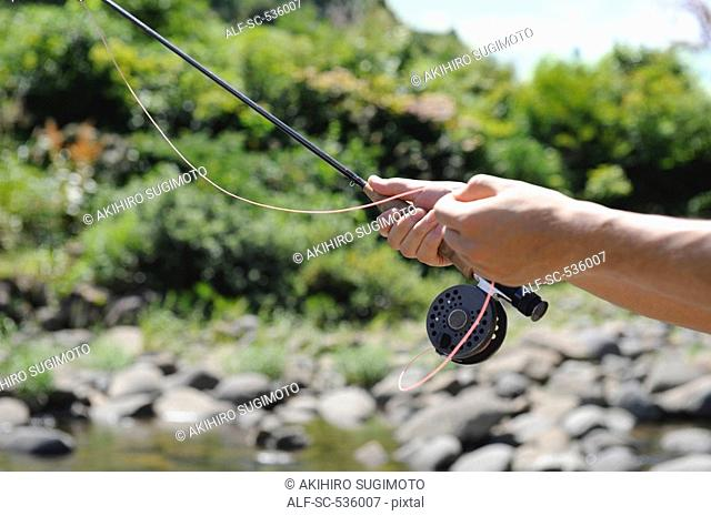 Hands holding fishing rod