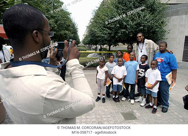 """Etan Thomas of the Washington Wizards poses for a picture with fans during the DC Hip Hop Theatre Festival, during the Fest's """"Poetry Slam"""""""