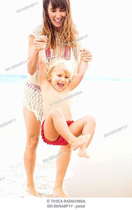 Mother swinging child on beach