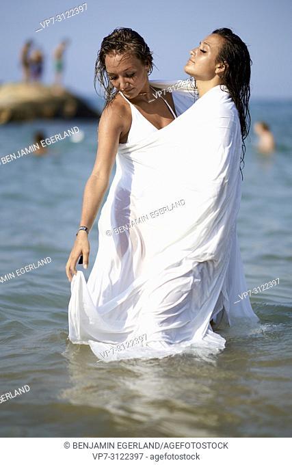 two sensual women shrouded in white blanket sheet, in sea, best friends, friendship goals, holidays. Chersonissos, Crete, Greece