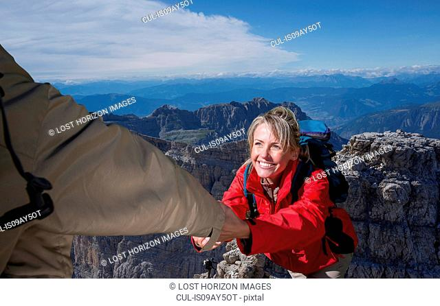 A male climber helping his female partner to reach the top of a mountain, Dolomites, Italy