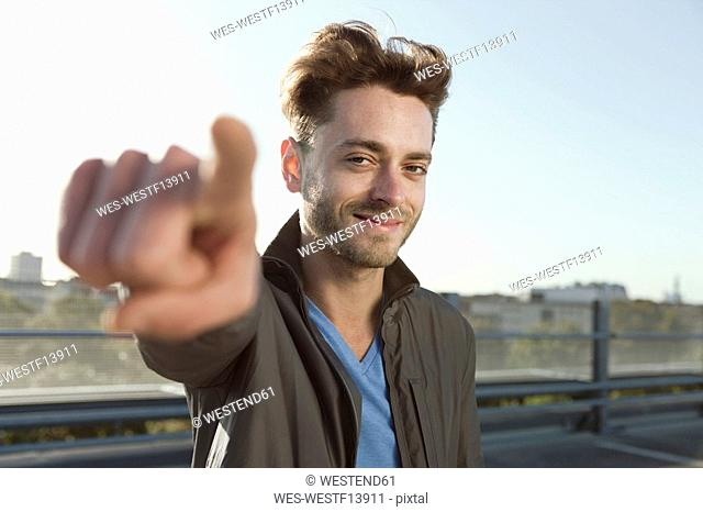 Germany, Berlin, Young man smiling and pointing, close-up, portrait