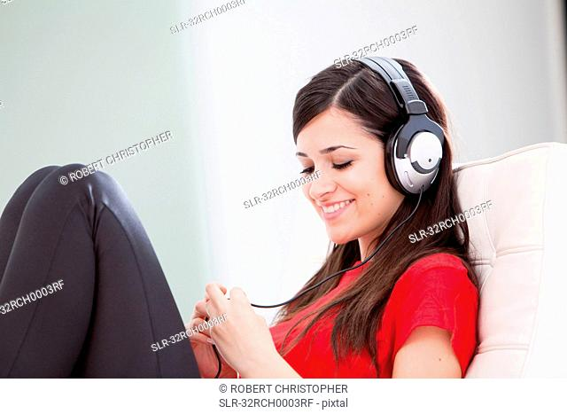 Woman listening to headphones on couch