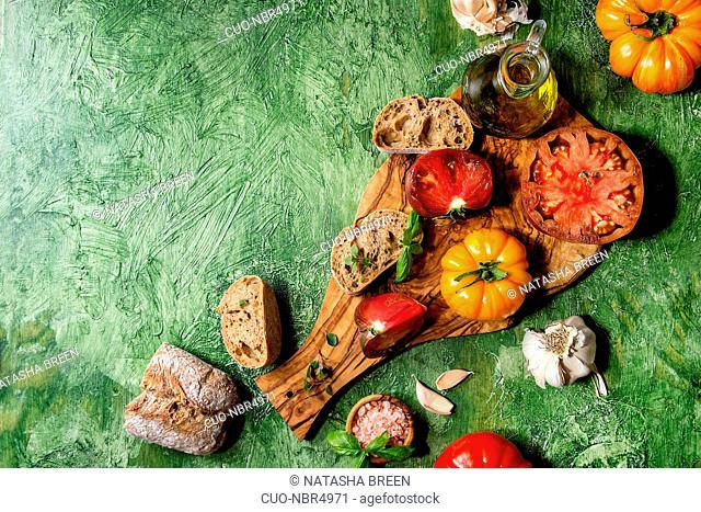 Variety of red and yellow organic tomatoes with olive oil, garlic, salt and bread for salad or bruschetta on wooden cutting board over green texture background