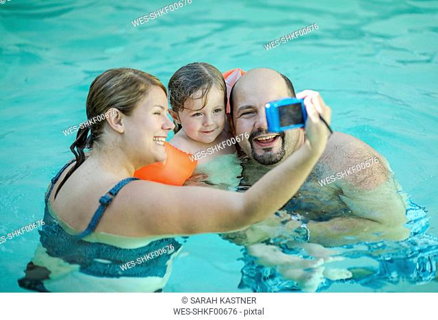 Family taking selfie in swimming pool
