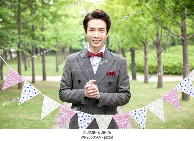 Young smiling groom folding hands outdoors