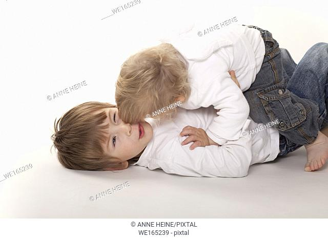 two boys embracing, lying on floor,white background