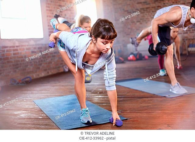 Exercise class balancing with dumbbells in gym studio