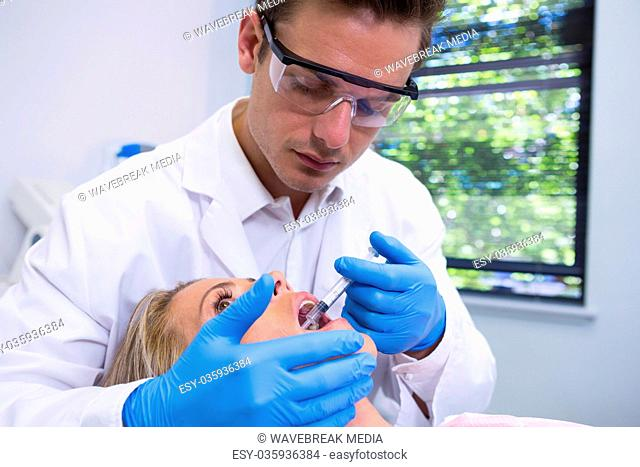 Dentist giving anesthetic to woman at medical clinic