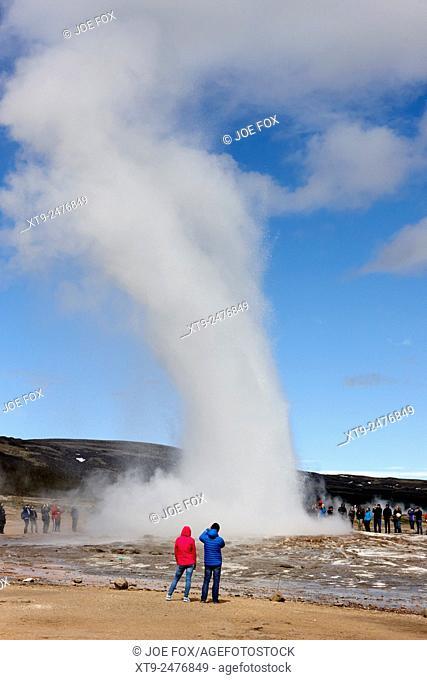tourists photograph strokkur geyser erupting at geyser geothermal site Geysir Iceland