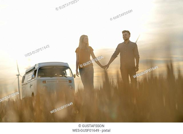 Young couple hand in hand at camper van in rural landscape at sunset