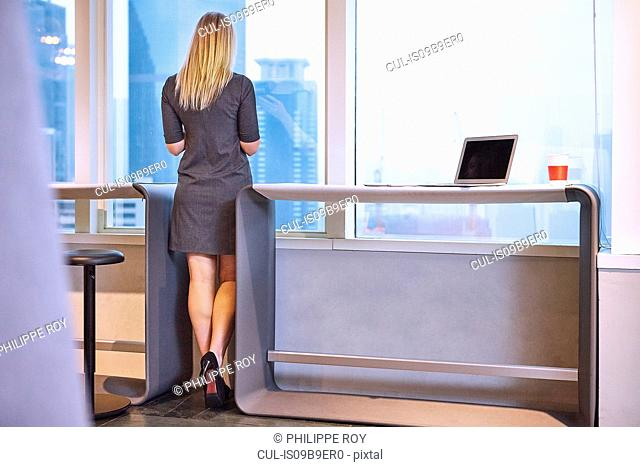 Full length rear view of businesswoman looking out of window