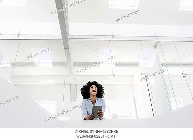 Young woman with tablet screaming in office