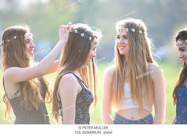 Teenage girls putting on and wearing daisy chain headdresses in park