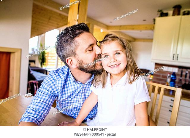 Father kissing his little daughter in kitchen