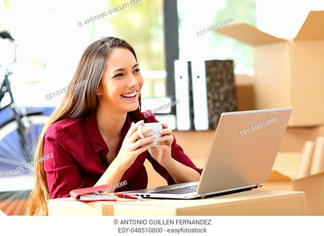Entrepreneur moving office working on line with a laptop and thinking holding a coffee cup with her belongings in carton boxes in the background