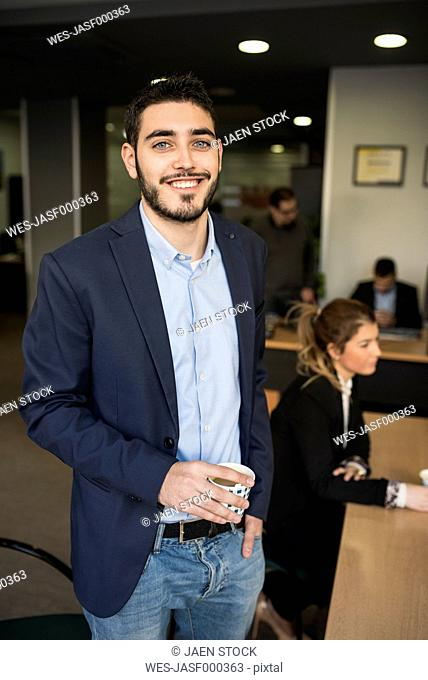 Smiling young man drinking coffee at office