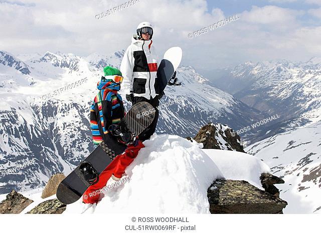 Snowboarders on rocky mountaintop
