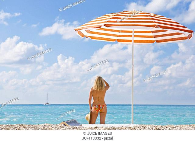 Woman in bikini on beach looking at ocean view near striped beach umbrella